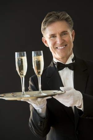Portrait of happy waiter in tuxedo holding serving tray with champagne flutes against black background photo