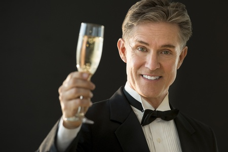 Portrait of happy mature man in tuxedo holding champagne flute against black background photo