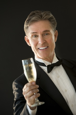 Portrait of happy mature man in tuxedo toasting champagne flute while standing against black background photo