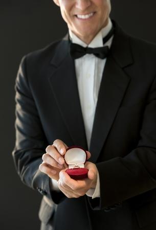 anillos de boda: Sección media de un hombre maduro feliz en la caja del anillo de retención esmoquin contra el fondo negro