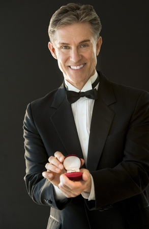 Portrait of happy mature man in tuxedo holding ring box isolated on black background photo