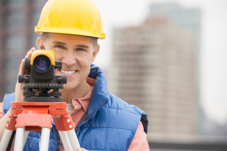 cartographer: Portrait of happy mature construction worker with theodolite standing at construction site