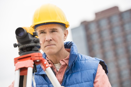 architect tools: Confident mature construction worker with theodolite looking away while at standing construction site