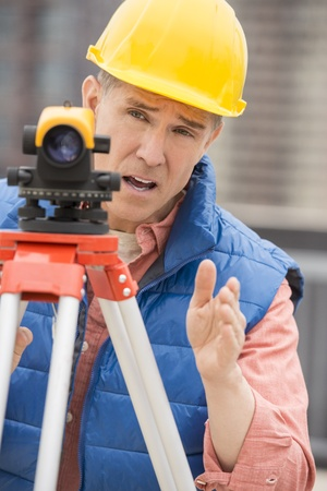 cartographer: Mature cartographer gesturing while using theodolite at construction site