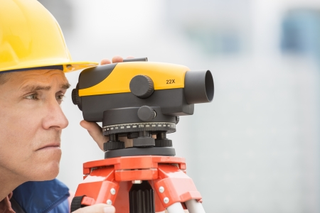 cartographer: Mature cartographer measuring distances through theodolite at construction site Stock Photo