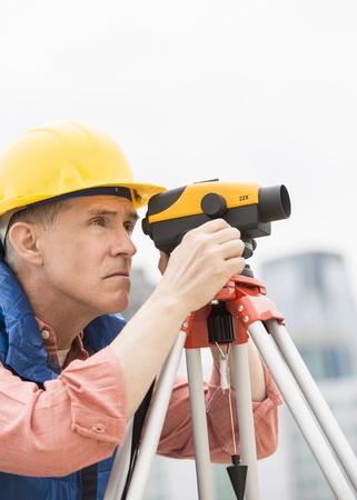 distances: Mature construction worker measuring distances through theodolite at site