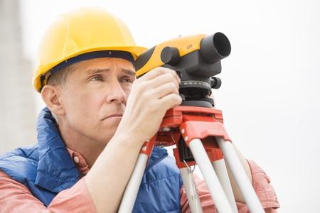 distances: Mature surveyor measuring distances through theodolite at construction site