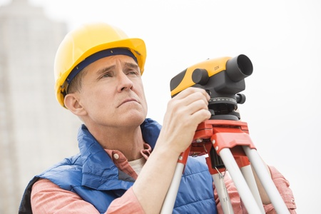 cartographer: Mature cartographer with theodolite looking away at construction site Stock Photo