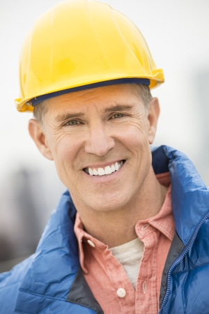 Close-up portrait of happy construction worker at site