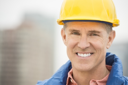 Close-up portrait of happy manual worker at construction site Standard-Bild