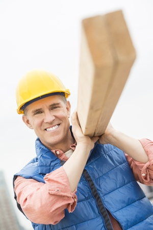 Portrait of happy construction worker carrying wooden plank on shoulder photo