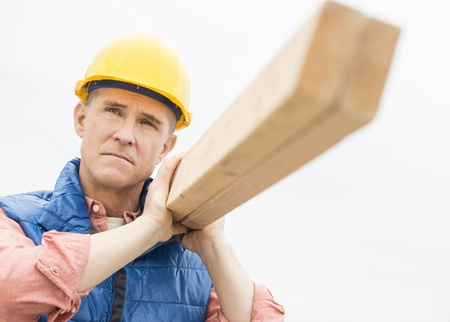 Thoughtful construction worker carrying wooden plank against clear sky