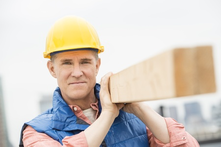Portrait of confident manual worker carrying wooden plank on shoulder photo