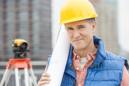 Portrait of confident male architect holding rolled up blueprint at construction site photo