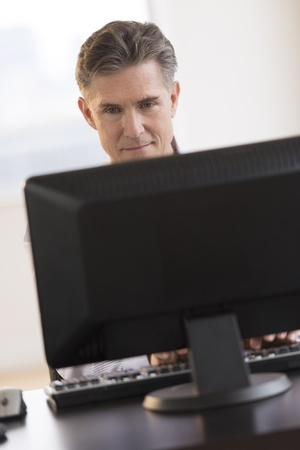 Mature businessman smiling while looking at computer monitor at desk in office photo