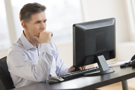working on computer: Mature businessman with hand on chin working on Desktop PC in office