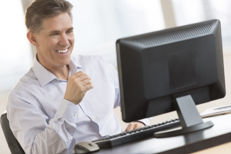 working on computer: Happy mature businessman looking at computer monitor at desk in office Stock Photo