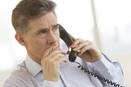 Thoughtful mature businessman looking away while using landline phone in office Standard-Bild