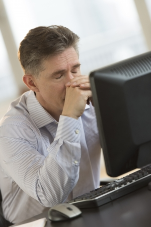 Exhausted mature businessman with eyes closed leaning on computer desk in office photo