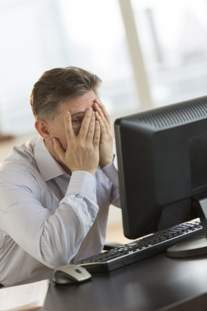Frustrated mature businessman with hands on face looking at computer at desk in office photo