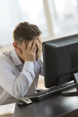 Tired mature businessman with hands on face leaning on computer desk in office photo