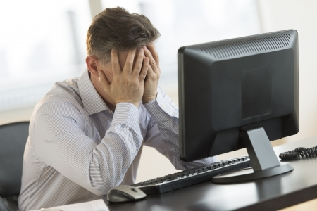 Stressed mature businessman with hands on face leaning on computer desk in office