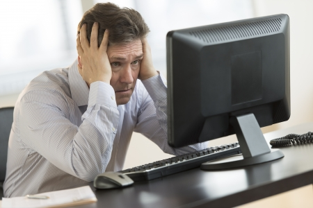 Exhausted mature businessman leaning while looking at computer monitor in office photo