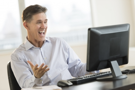 man using computer: Excited mature businessman shouting while using Desktop PC in office Stock Photo