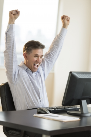 white achievement: Successful mature businessman with arms raised screaming while using computer in office