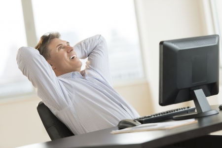 arms behind head: Happy mature businessman with hands behind head looking up while sitting at desk in office