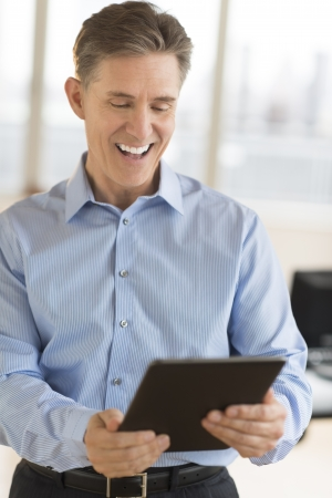 only men: Cheerful mature businessman using digital tablet in office