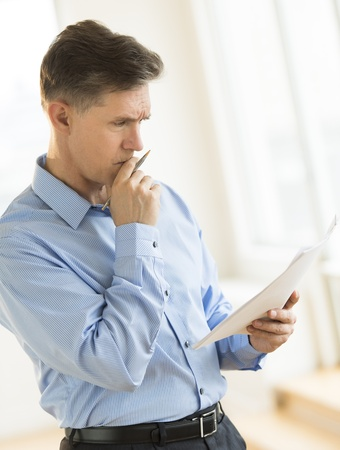 Serious mature businessman reading document while standing in office