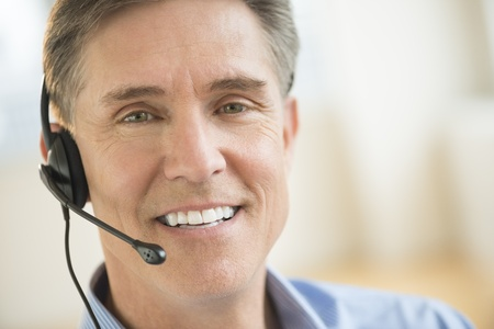 Close-up portrait of confident male customer service representative wearing headset photo