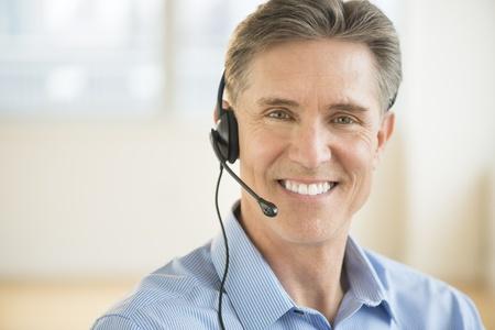Portrait of happy mature male customer service representative wearing headset