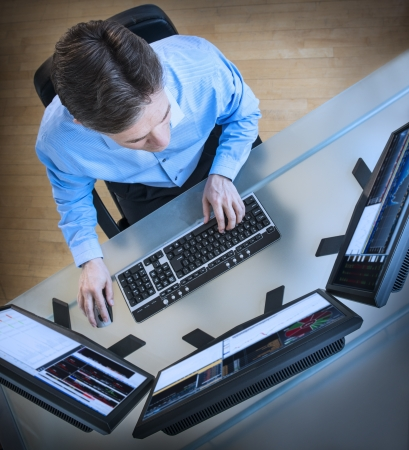 High angle view of mature male trader analyzing data on multiple screens at desk in office Standard-Bild