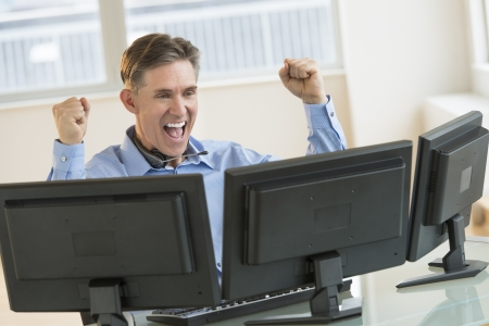 Successful mature male trader screaming while using multiple computers at desk in office