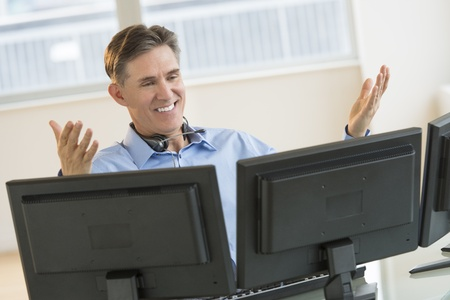 Happy mature male trader gesturing while using multiple screens at desk in office Stock Photo - 22079750
