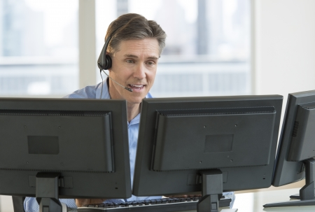 service desk: Happy mature male customer service representative using multiple screens at desk in office