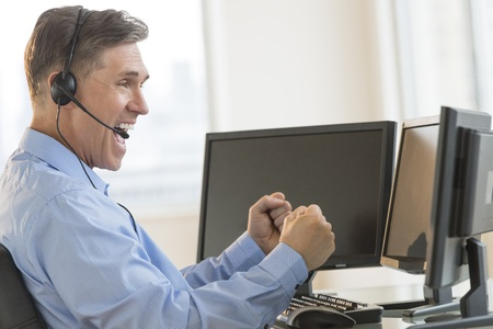 Side view of excited mature male trader screaming while using multiple computers at desk in office Stock Photo - 22079749