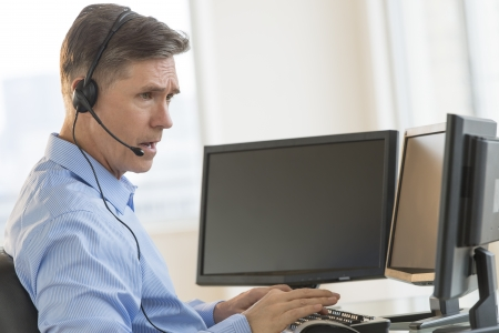 Side view of male trader using multiple computer screens while communicating through headphones at desk Standard-Bild