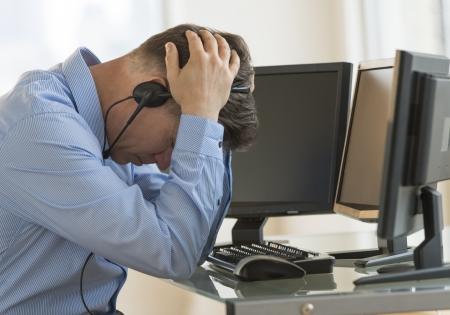 cansancio: Perfil tirado de comerciante agotado hombre con la cabeza en las manos apoyándose en escritorio de la computadora en la oficina