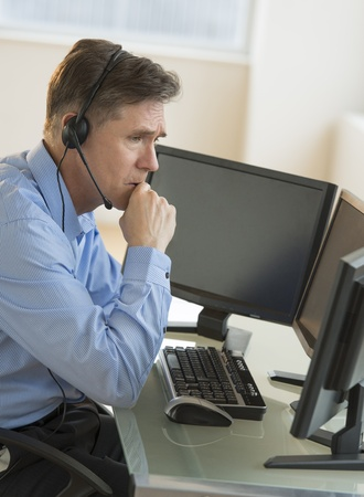 Side view of male customer service representative with hand on chin looking at computer monitors at desk Stock Photo - 22079758