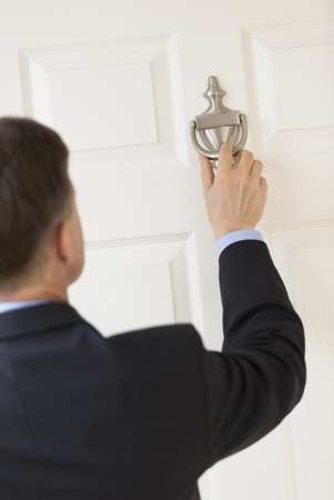 knocking: Rear view of mature businessman knocking door handle Stock Photo