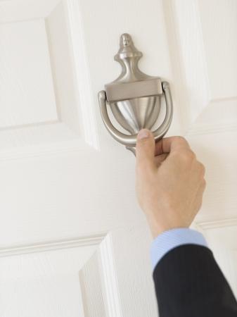 cerrar la puerta: Recorta la imagen de la mano del hombre de negocios maduro llamando manija de la puerta