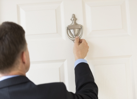 handle: Rear view of mature businessman knocking door knocker