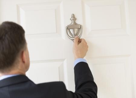 cerrar la puerta: Vista posterior de hombre de negocios maduro golpear aldaba Foto de archivo