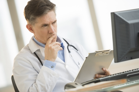 serious doctor: Serious mature male doctor looking at computer monitor while holding clipboard at desk in clinic
