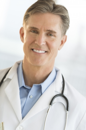 Close-up portrait of confident mature male doctor smiling photo