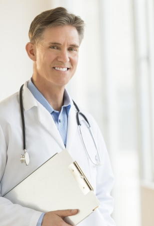 Portrait of happy mature male doctor holding clipboard while standing in clinic