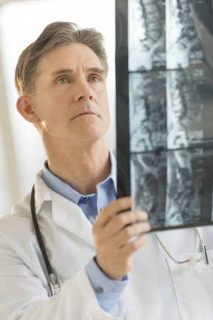 Mature male doctor examining X-ray image in clinic photo